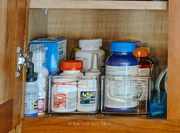 Medicine and vitamins organized into bins, but they didn't quite fit.