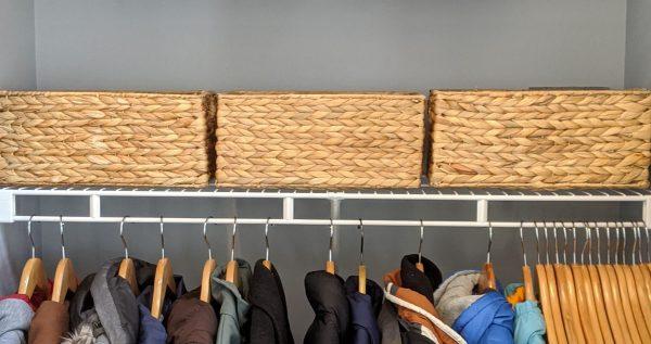 Using bins can be helpful for coat closet organization.