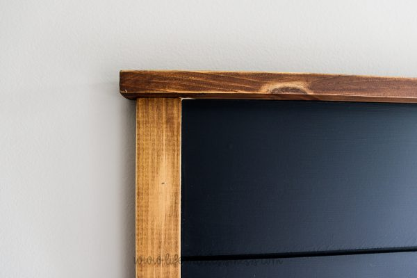 Stained wooden frame and black shiplap headboard.